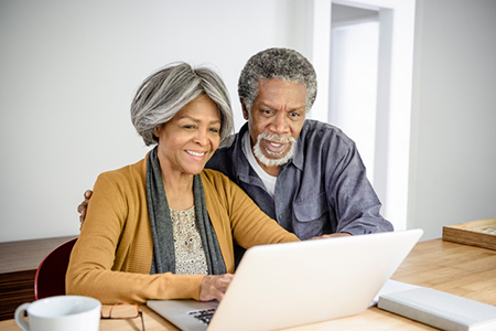 Senior African American couple using laptop together at home
